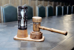 Wooden hourglass and mallet on the table Stock Images
