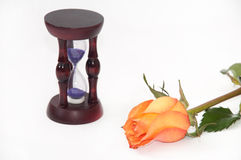 Wooden hourglass and orange rose on the white background Royalty Free Stock Image