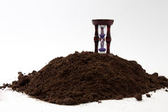 Wooden hourglass on the soil ground.  Stock Photo