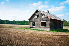 Wooden house. Sad sight of  empty windows of an abandoned wooden house, against a plowed field - Podlachia / Poland Stock Images