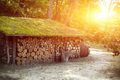 Wooden house with accurately precisely gathered together firewood logs. With beutiful sunset on the background Stock Photos