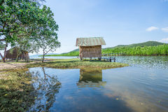 Wooden house along the lush riverside Stock Photo