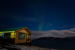 Wooden house on the background of the aurora Royalty Free Stock Images