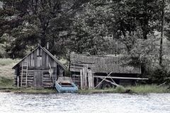 Wooden house, barn of fisherman, motor boat. Dying Russian village Royalty Free Stock Photo