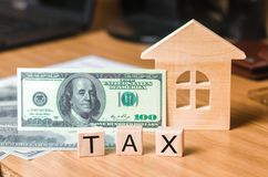 Wooden house and a bill of one hundred dollars, inscription taxes. Concept of property taxes, purchase and sale of property. Stock Photo