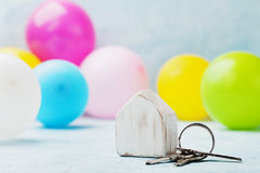 Wooden house with bunch of keys and air balloons on light table. Housewarming, moving, real estate or buying a new home concept. Royalty Free Stock Photos