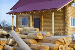 Wooden house and a bunch of logs Stock Images