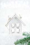 Wooden house christmas decoration on white snow background Royalty Free Stock Images