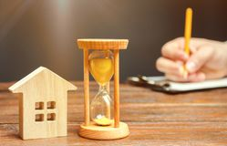 Wooden house and clock. A person signs documents. Signing a contract to rent a house or apartment. Making a will. Testament stock photography