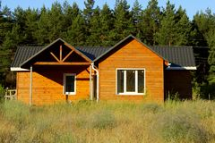 Beautiful Modern Wooden House, Front Elevation. Front View. Wooden House In Countryside. Ecological Small Wooden House. Wooden House With Meadow In Front Of It Royalty Free Stock Photography