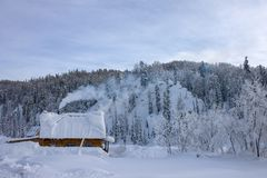 Snow-covered wooden house on the background of mountains and forests royalty free stock photography
