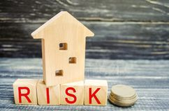 Wooden house and cubes with the word `risk`. The concept of risk, loss of real estate. Property insurance. Loans secured by home,. Apartment. Financial risks stock images