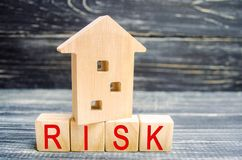 Wooden house and cubes with the word `risk`. The concept of risk, loss of real estate. Property insurance. Loans secured by home,. Apartment. Financial risks royalty free stock photography