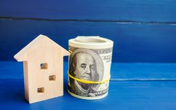 Wooden house and dollars on a blue background. concept of real estate. buying, selling, renting. credit for property. sale apartme. Nt. mortgage. affordable stock photography
