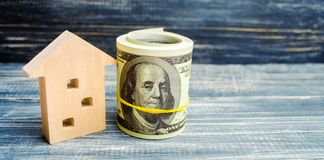 Wooden house and dollars on a blue background. concept of real estate. buying, selling, renting. credit for property. sale apartme. Nt. mortgage. affordable stock images
