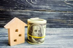 Wooden house and dollars on a blue background. concept of real estate. buying, selling, renting. credit for property. sale apartme. Nt. mortgage. affordable royalty free stock image