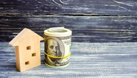 Wooden house and dollars on a blue background. concept of real estate. buying, selling, renting. credit for property. sale apartme. Nt. mortgage. affordable royalty free stock photo
