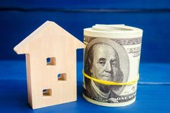 Wooden house and dollars on a blue background. concept of real estate. buying, selling, renting. credit for property. sale apartme. Nt. mortgage. affordable stock image