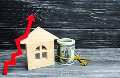 Wooden house, dollars and keys with a red arrow up. concept of high demand for real estate. increase energy efficiency of housing. Rise in house prices stock images