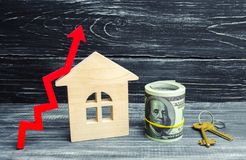 Wooden house, dollars and keys with a red arrow up. concept of high demand for real estate. increase energy efficiency of housing. Rise in house prices stock photography