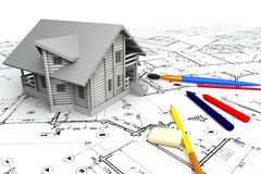 Wooden house on the drawings with stationery Royalty Free Stock Photography