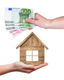 Wooden house and Euro banknotes in hands Stock Photography