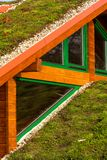 Wooden house with extensive green living roof covered with vegetation. Wooden house with extensive green ecological living sod roof covered with vegetation stock photography