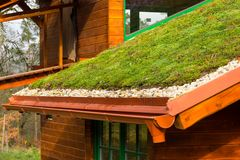 Wooden house with extensive green living roof covered with vegetation. Wooden house with extensive green ecological living sod roof covered with vegetation royalty free stock photos