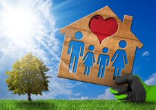 Wooden House with Family on Green Grass. Hand with work glove holding a wooden model house with a family and heart on green grass with a tree, blue sky with Stock Photography