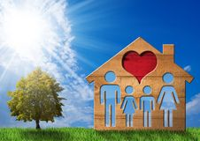 Wooden House with Family on Green Grass. Wooden model house with a symbol of family and heart on green grass with a tree and a blue sky with clouds and sun rays Stock Image