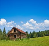 Wooden house on a field Royalty Free Stock Photos
