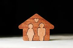 Wooden house with figures of man and woman inside. On black background with blank space for text stock image