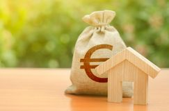 Wooden house figurine and Euro money bag on the background of nature. Budget, subsidized funds. Mortgage loan for the purchase. Of housing, construction or stock images