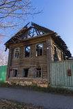 The wooden house after the fire. The burned-down wooden house on the old street against the clear blue sky Stock Photography