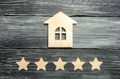 Wooden house and five stars on a gray background. Rating of houses and private property. Buying and selling, renting apartments. T. He level of the restaurant royalty free stock photography
