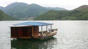 Wooden house floating on river