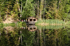 Wooden house in the forest above the lake with reflection. Stock Image