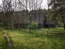 Wooden house in forest . Country house . Cottage behind a wooden fence in the trees. royalty free stock photography