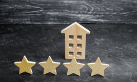 Wooden house and four stars on a gray background. Rating of houses and private property. Buying and selling, renting apartments. The level of the restaurant stock photos