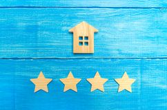Wooden house and four stars on a gray background. Rating of houses and private property. Buying and selling, renting apartments. T. He level of the restaurant royalty free stock photo