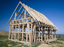 Wooden house frame. A new wooden house being constructed, the frame  looks contrasty on saturated blue sky background Royalty Free Stock Images