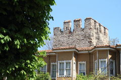 Wooden house in front of fortification. Tower with battlements in Istanbul, Turkey Stock Images