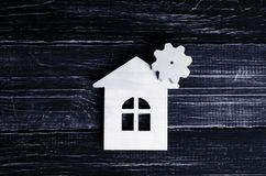 Wooden house with a gear on a background of dark wood. The concept of the enterprise for production, manufactory. Repair and automation, smart house of the stock photo