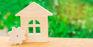 Wooden house and gear. Concept of project development. Energy efficiency at home, new technologies and innovations. Industrial com. Plex or sector. Scope of royalty free stock image