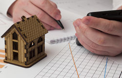 Wooden house in the graphs and male hand with phone Stock Photo