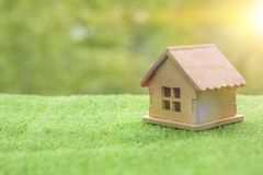 A wooden house on the grass, against a background of greenery. Royalty Free Stock Photos