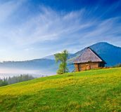 Wooden house on a green hill Stock Images