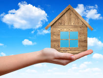 Wooden house in hand Royalty Free Stock Image