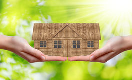 Wooden house in hands Stock Image