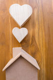 Wooden house and heart on brown wood Royalty Free Stock Images